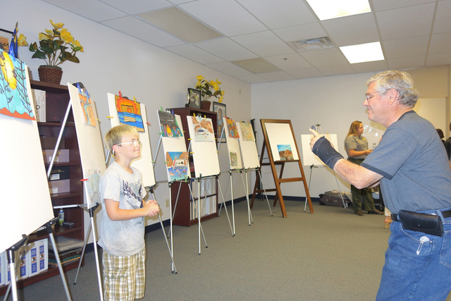 Artist is Logan Beatey stands by winning art displayed on easels during the reception honoring art contest winners of the Every Kid in a Park contest. Diane Taylor/Special to View