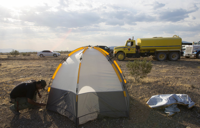Fernando Reyes, with the Nevada Division of Forestry, assembles his tent at a base camp for fire crews fighting the Lovell wildfire near state Route 160 and Lovell Canyon Road on Monday, June 27,  ...