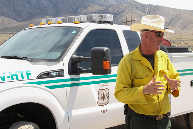 Ray Johnson, a fire prevention officer with the U.S. Forest Service, speaks with a member of the media about the 250-acre wildfire near State Route 160 and Lovell Canyon Road on Monday, June 27, 2 ...