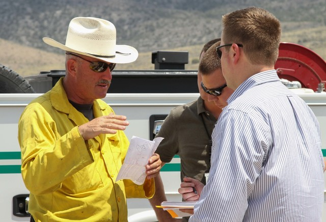 Ray Johnson, left, a fire prevention officer with the U.S. Forest Service, speaks with Las Vegas police officers investigating the wildfire near state Route 160 and Lovell Canyon Road on Monday, J ...