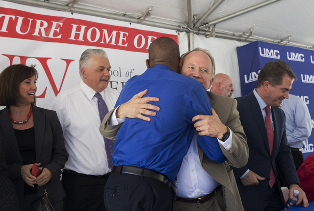 Michael Wixom, vice chairman of the Board of Regents, hugs Clark County Commissioner Lawrence Weekly during an event to commemorate the commission's decision to give UNLV a 9-acre plot of land to  ...