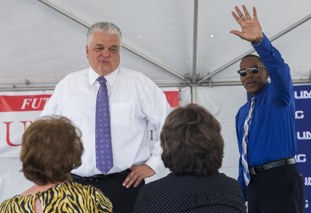 Clark County Commission Chairman Steve Sisolak, left, and Clark County Commissioner Lawrence Weekly socialize with guests before the start of a ceremony to commemorate the commission's decision to ...