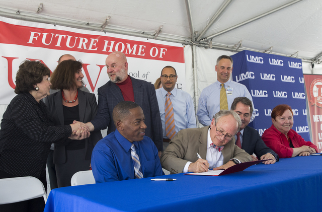 Clark County Commissioner Lawrence Weekly, left, and Michael Wixom, vice chairman of the Board of Regents, sign a ceremonial deed transfer during an event to commemorate the commission's decision  ...