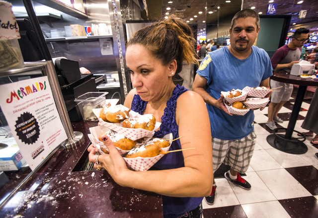 Melissa Harris, left, and  Daniel Torres carry deep fried Twinkies and Oreo cookies at  Mermaid's Casino, 32 Fremont St., on Tuesday, June 21, 2016. The casino, famous for cheap fried food, will b ...