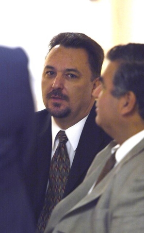 Tony Dane, center, waits in the hallway outside the state grand jury room in Las Vegas, Feb. 24, 2004, where the Moncrief election fraud hearing is being held. Attorney Don Chairez is seated at ri ...