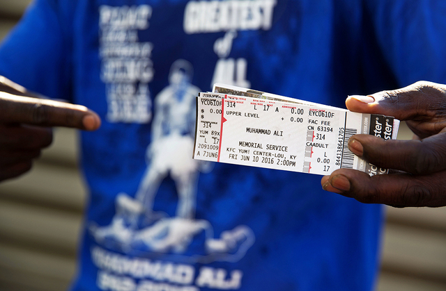 Montez Jones, of Louisville, shows off his tickets to Muhammad Ali's memorial service Friday at the KFC Yum! Center after waiting in line Wednesday, June 8, 2016, in Louisville, Ky. Ali's memorial ...