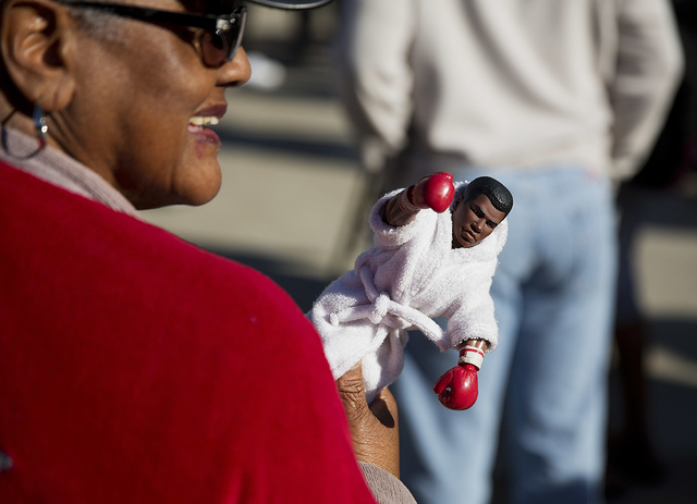 Barbara Hillman, of Louisville, carries a Muhammad Ali doll after receiving tickets to Ali's memorial service Friday at the KFC Yum! Center Wednesday, June 8, 2016, in Louisville, Ky. Ali's memori ...