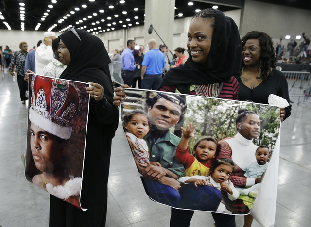 Mourners hold photos of Muhammad Ali after his Jenazah, a traditional Islamic Muslim service, in Freedom Hall, Thursday, June 9, 2016, in Louisville, Ky. (Darron Cummings/AP)