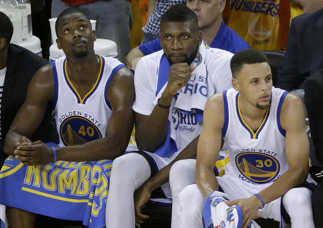 Golden State Warriors forward Harrison Barnes, from left, center Festus Ezeli and guard Stephen Curry sit on the bench during the second half of Game 5 of basketball's NBA Finals against the Cleve ...