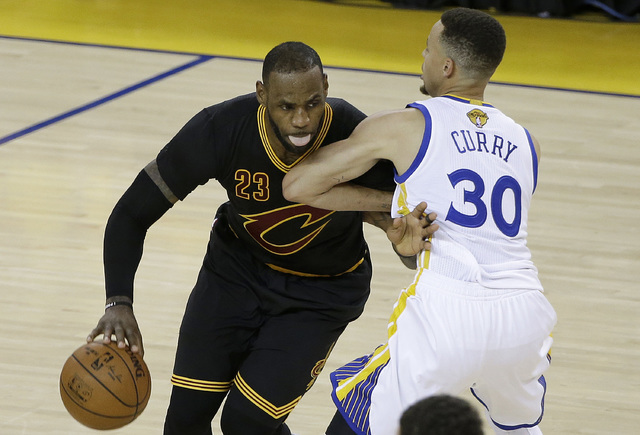 Cleveland Cavaliers forward LeBron James (23) dribbles against Golden State Warriors guard Stephen Curry (30) during the second half of Game 5 of basketball's NBA Finals in Oakland, Calif., Monday ...
