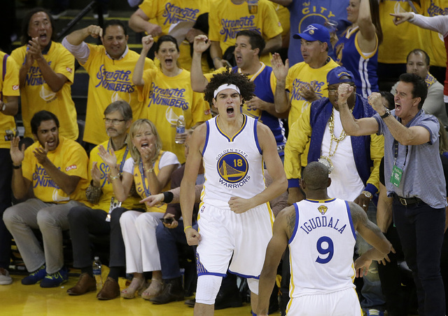 Golden State Warriors forward Anderson Varejao (18) and forward Andre Iguodala (9) react during the second half of Game 5 of basketball's NBA Finals against the Cleveland Cavaliers in Oakland, Cal ...