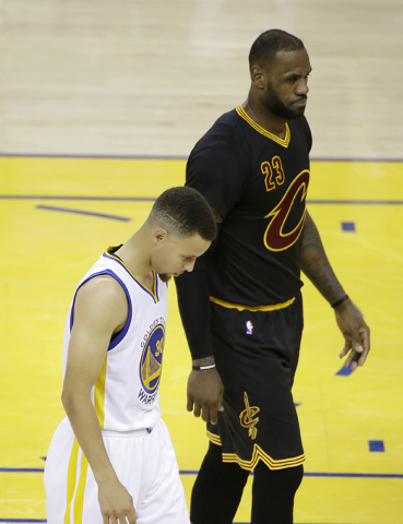 Golden State Warriors guard Stephen Curry, left, walks next to Cleveland Cavaliers forward LeBron James (23) during the second half of Game 5 of basketball's NBA Finals in Oakland, Calif., Monday, ...