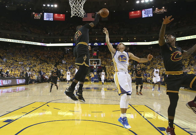 Cleveland Cavaliers forward LeBron James (23) defends a shot by Golden State Warriors guard Stephen Curry (30) during the first half of Game 5 of basketball's NBA Finals in Oakland, Calif., Monday ...