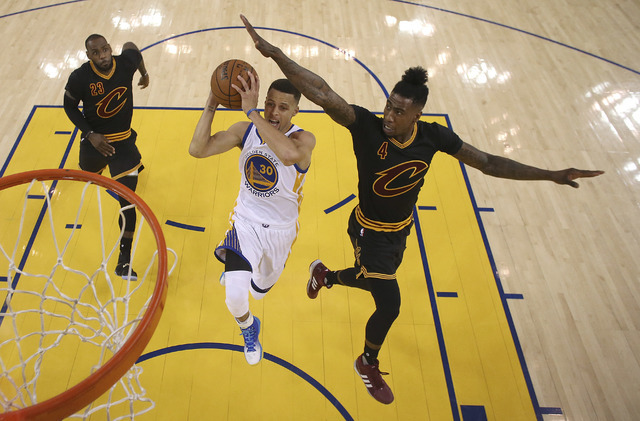 Golden State Warriors guard Stephen Curry (30) shoots between Cleveland Cavaliers forward LeBron James (23) and guard Iman Shumpert (4) during the first half of Game 5 of basketball's NBA Finals i ...