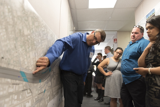 Jay Proskovec, public affairs manager for PCCP Constructors, left, discusses Project Neon with preview event attendees at the Spaghetti Bowl construction project's trailer at 320 Wall St. in Las V ...