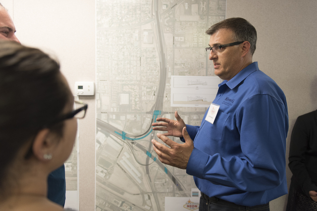 Jay Proskovec, public affairs manager for PCCP Constructors, right, discusses Project Neon with preview event attendees at the Spaghetti Bowl construction project's trailer at 320 Wall St. in Las  ...