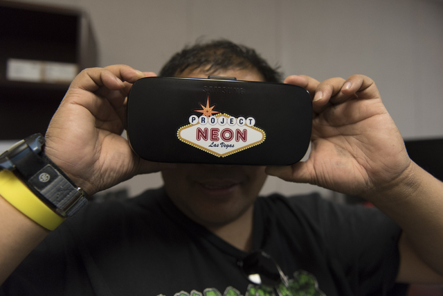 Erick Farrales looks through VR goggles to view a helicopter flyover simulation of the Project Neon site during a preview event at the Spaghetti Bowl construction project's trailer at 320 Wall St. ...