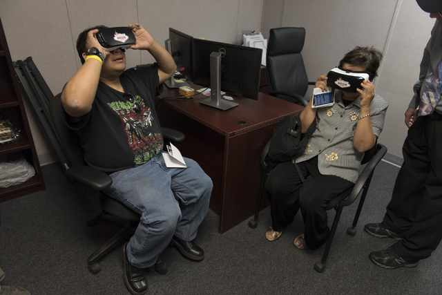 Erick Farrales, left, looks through VR goggles to view a helicopter flyover simulation of the Project Neon site during a preview event at the Spaghetti Bowl construction project's trailer at 320 W ...