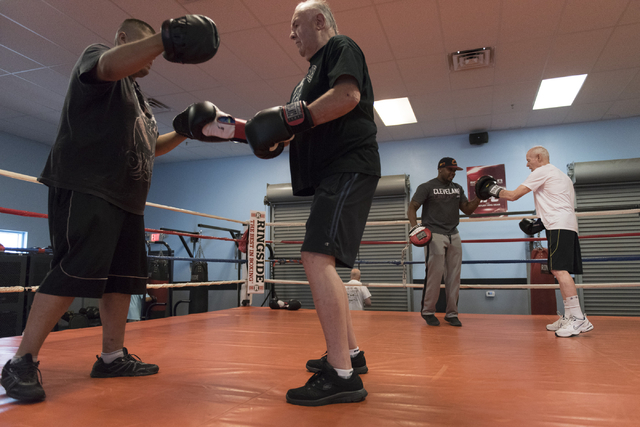 Jerry Sloan, second from left, and Stephen Long, right, do punching exercises with instructors Alvaro Morales, left, and Donche King, third from left, during the Rock Steady Boxing Program at Rich ...
