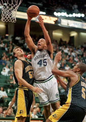In this March 14, 2000, file photo, Dallas Mavericks' Sean Rooks (45) shoots the ball over Indiana Pacers' Zan Tabak, left. and Jalen Rose (5) during the fourth quarter of an NBA basketball game i ...