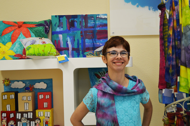 Amanda D. poses for a picture in the Artworks Studio Store at Opportunity Village in June 2016. Her painting is featured near one of the entrances of Dillard's in Downtown Summerlin as part of a ...