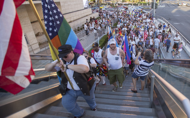 People march during a gathering on the Las Vegas Strip to show their solidarity for the victims of the Pulse nightclub shooting in Orlando, Fla., in Las Vegas on Monday, June 20, 2016. Richard Bri ...