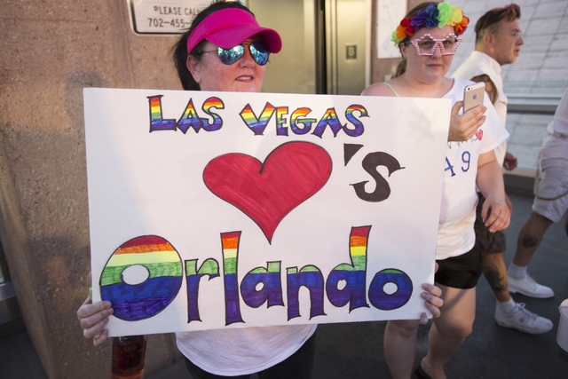 A marcher raises a placard as members of the community gather on the Las Vegas Strip to show their solidarity for the victims of the Pulse nightclub shooting in Orlando, Fla., in Las Vegas on Mond ...