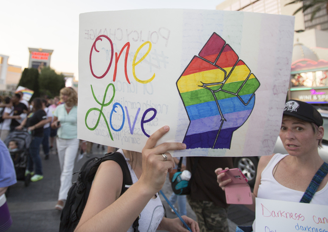 A marcher raises a sign as members of the community gather on the Las Vegas Strip to show their solidarity for the victims of the Pulse nightclub shooting in Orlando, Fla., in Las Vegas on Monday, ...