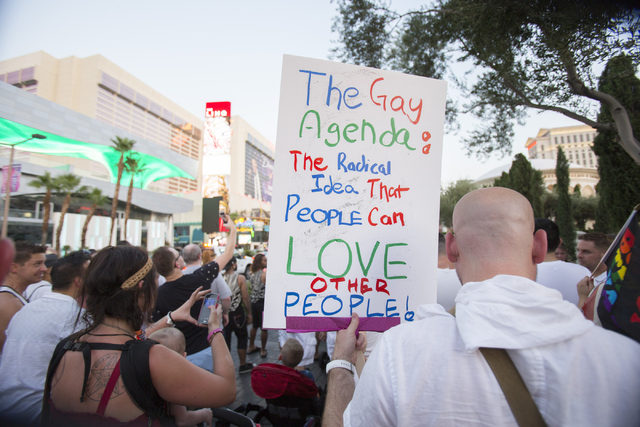 A marcher carries a sign as members of the community gather on the Las Vegas Strip to show their solidarity for the victims of the Pulse nightclub shooting in Orlando, Fla., in Las Vegas on Monday ...