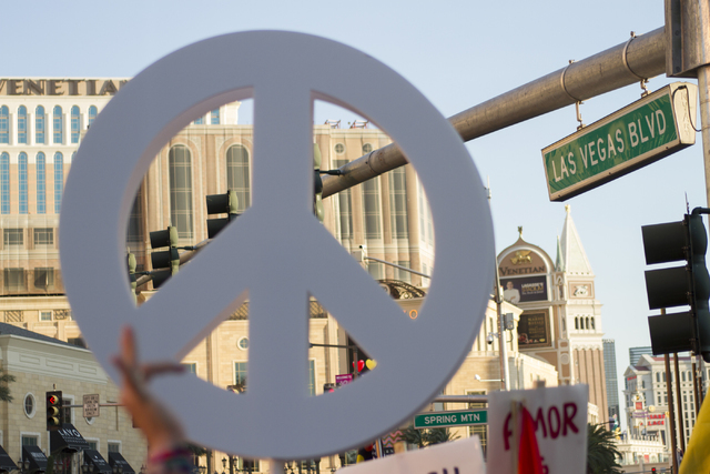 A marcher raises a peace sign as members of the community gather on the Las Vegas Strip to show their solidarity for the victims of the Pulse nightclub shooting in Orlando, Fla., in Las Vegas on M ...