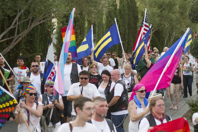 People are seen marching as members of the community gather on the Las Vegas Strip to show their solidarity for the victims of the Pulse nightclub shooting in Orlando, Fla., in Las Vegas on Monday ...
