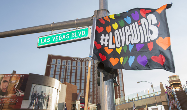 A marcher raises a flag as members of the community gather on the Las Vegas Strip to show their solidarity for the victims of the Pulse nightclub shooting in Orlando, Fla., in Las Vegas on Monday, ...