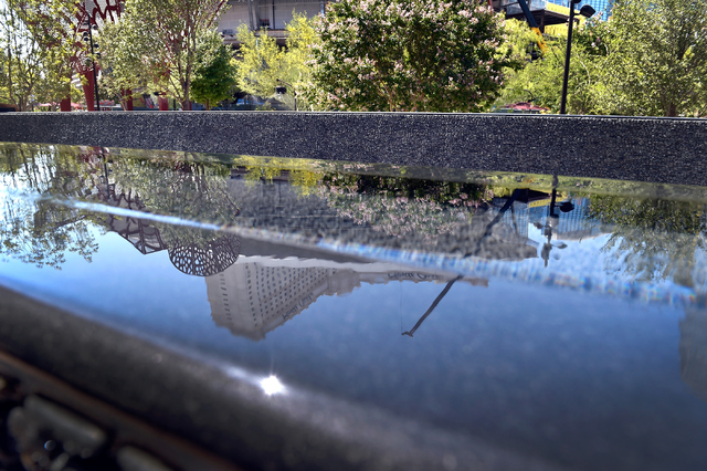 The Monte Carlo hotel-casino is seen reflected in a water feature at The Park Friday, June 3, 2016, in Las Vegas. MGM Resorts International announced the Monte Carlo will be transformed into two h ...