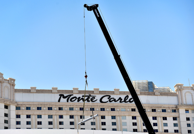 A construction crane lowers a piece of pipe near the Monte Carlo hotel-casino Friday, June 3, 2016, in Las Vegas. MGM Resorts International announced the Monte Carlo will be transformed into two h ...