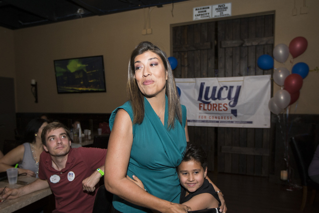 Democratic Congressional District 4 candidate Lucy Flores  embraces her nephew Sean Andrew Bleu Bordens as she speaks to supporters during her election night party at Aces & Ales on Tuesday, J ...
