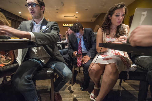 Steven Conger Jr., assistant campaign manager, from left, Democratic Congressional District 3 candidate Jesse Sbaih, and campaign manager Angie Morelli look at election results during a campaign e ...