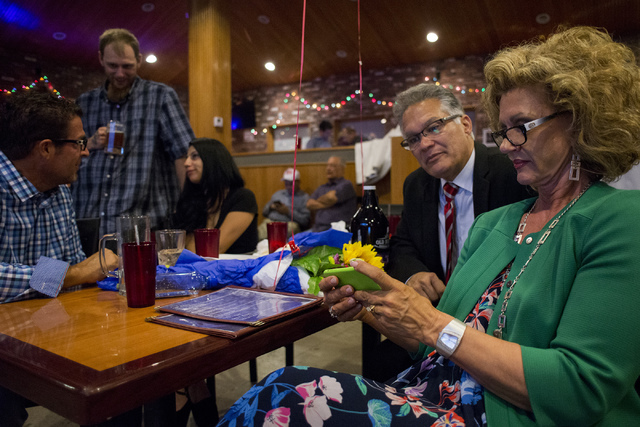 Nevada Republican National Committeewoman and Assembly candidate Diana Orrock checks results on her phone as Assembly candidate Tony Baca peaks over her shoulder at Old School Brewing Company in L ...
