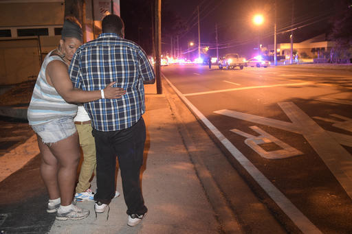 Bystanders wait down the street from a multiple shooting at the Pulse nightclub in Orlando, Fla., Sunday, June 12, 2016. A gunman opened fire at a nightclub in central Florida, and multiple people ...