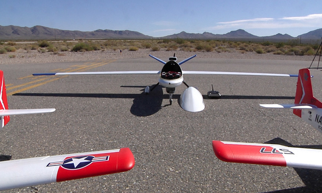 The Sandstorm UAV, an experimental unmanned aircraft system manufactured by Unmanned Systems, Inc., sits between two T-28 trainers at Desert Rock Airport at the Nevada National Security Site on Th ...