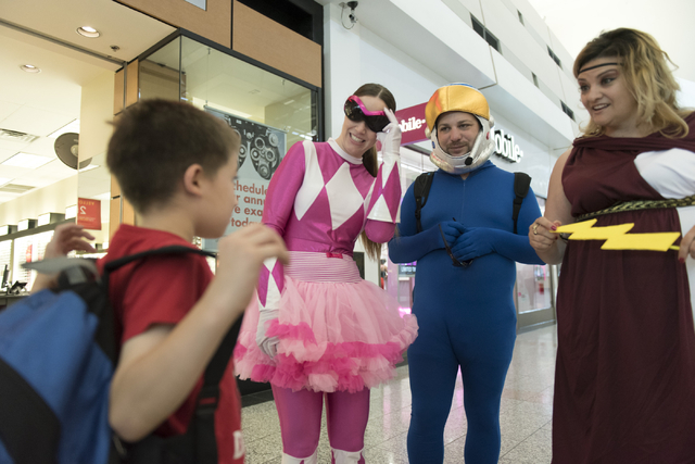From left, Anthony Schattilly, 7, is greeted by Bridget Lasorsa, Jonathan Speregon and Jamie Rodriguez, teachers with Daniel Goldfarb Elementary School, during the CCSDs Reading Rangers program ki ...
