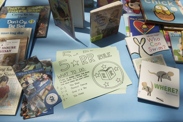 A card explaining the 5 star Reading Rangers rule sits on a table with books that are given away as prizes for completing activities during the Clark County School District's Reading Rangers progr ...