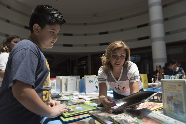Stevie Escalante, 9, left, is shown a book by Amarilis Rosario-Tillema, a volunteer with the National Charity League's Green Valley chapter, during the Clark County School District's Reading Range ...