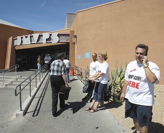 Political activist Tony Dane, right, talks on his cell phone while working with volunteers outside a DMV in Las Vegas, Sept. 8, 2003, where they are attempting to collect signatures for a recall e ...