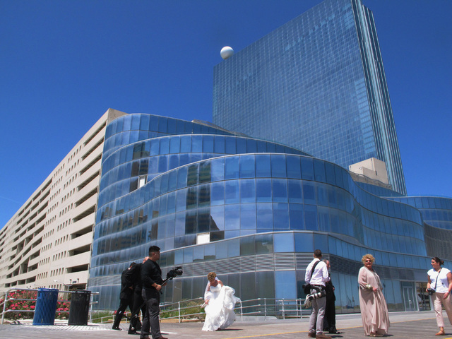 A wedding party searches for spots for a photo near the former Revel casino in Atlantic City, N.J., Friday, June 10, 2016. Revel and its next-door neighbor the Showboat both closed in 2014, and ar ...
