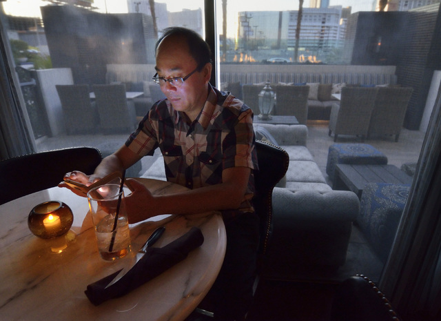 Jinquan Zhou, a professor from Macau Polytechnic Institute visiting Las Vegas for a conference, waits for dinner at the Barrymore restaurant and bar in the Royal Resort at 99 Convention Center Dri ...