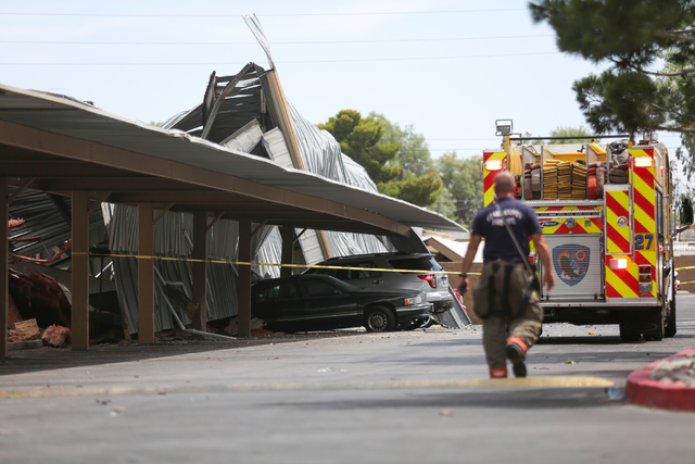 Clark County Fire Department workers tend to a roof collapse near the intersection of East Sahara Avenue and Boulder Highway on Thursday, June 9, 2016 in Las Vegas. The collapse damaged cars parke ...