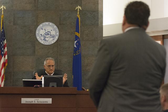 Louis C. Schneider, attorney for Desert Pines High School teacher Jonathan Scheaffer, right, speaks with Judge Joseph S. Sciscento, Scheaffer's court appearance at the Regional Justice Center in L ...
