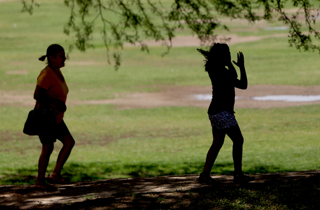 Francisca Sanchez, 41, and her daughter Karla Ortiz, 11, who don't want to show their face, walk at Nellis Meadows Park on Thursday, June 9, 2016, in Las Vegas. (Bizuayehu Tesfaye/Las Vegas Review ...