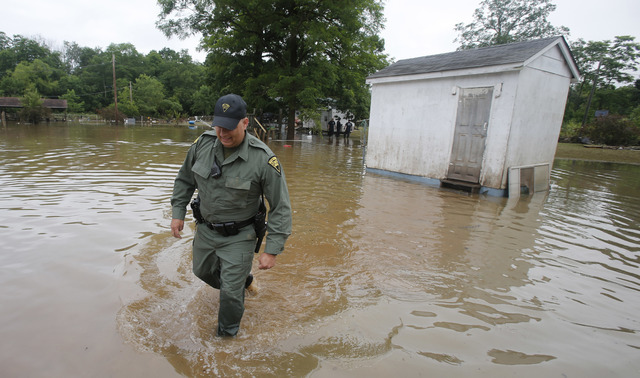 West Virginia State Trooper C.S. Hartman walks from a shed that he checked out as he and other crews search homes in Rainelle, W. Va., Saturday, June 25, 2016. (Steve Helber/The Associated Press)