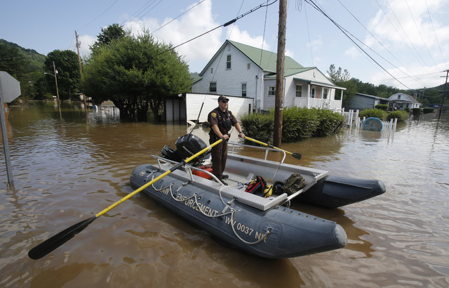 Lt. Dennis Feazell, of the West Virginia Department of Natural Resources, rows his boat as he and a co-worker search flooded homes in Rainelle, W. Va., Saturday, June 25, 2016. (Steve Helber/The A ...